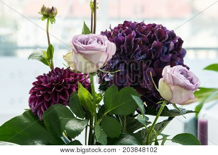 Close-up purple flowers in the vase on the table. Little bouquet made of pink roses and violet hydrangea flowers on light background. Beautiful floristic decor for event. Wedding decor