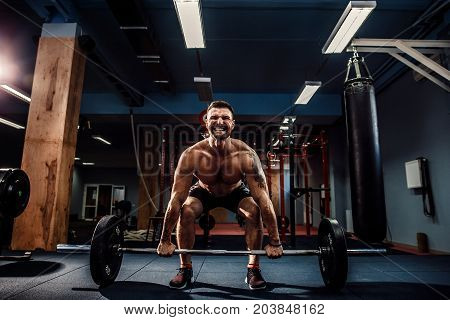 Muscular strong fitness man doing deadlift of a barbell in modern fitness center. Functional training. Snatch exercise. Scream for motivation