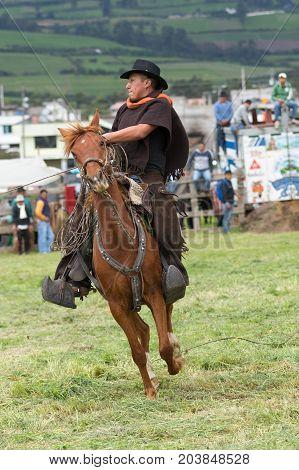 June 3 2017 Machachi Ecuador: closeup of Andean cowboy on horseback dressed traditionally on horseback working in field