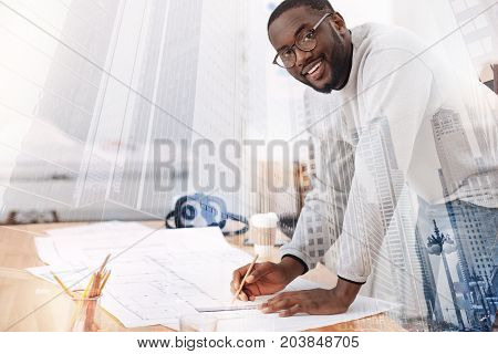 Brilliant worker. Close up of busy ambitious African American with glasses drawing sketches while leaning on the table