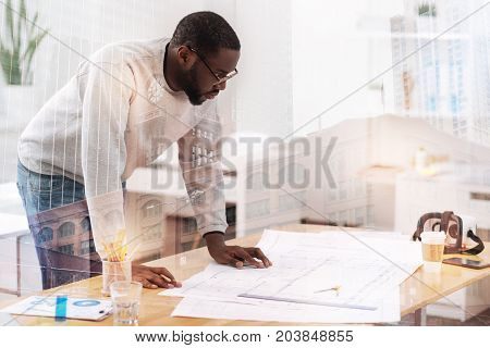 Correcting drawbacks. Waist up of attentive engineer leaning on the table while looking at his works and being concentrated