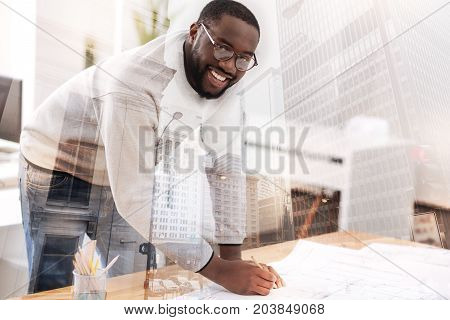 Diligent employee. Close up of ambitious bearded worker working at the table with sketches while expressing enjoyment