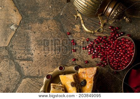 grains and seeds of pomegranate with a copper jug on an old decorative paving stone. an antique copper jug with a pomegranate and cake on an old tile