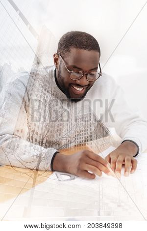 Exciting task. Close up of African American using a pencil and making drafts while sitting at the table