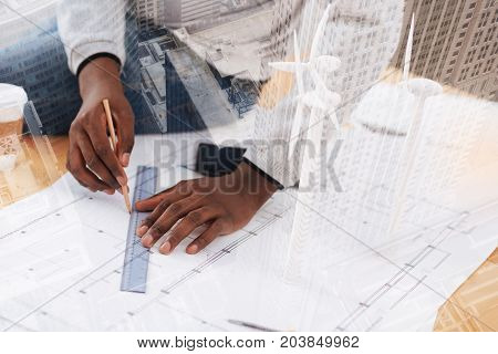 Step by step. Close up of young successful engineer working at the table and making measurements being fully concentrated