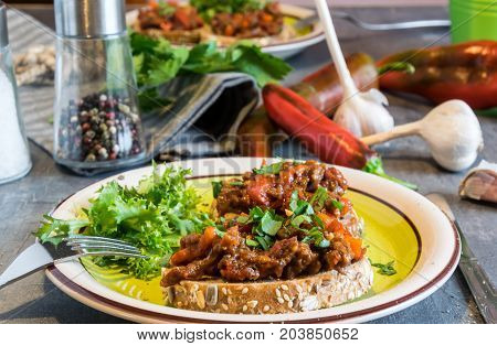 Beef meat mixture with tomatoes and pepper on fried bread, herbaceous. Great dinner
