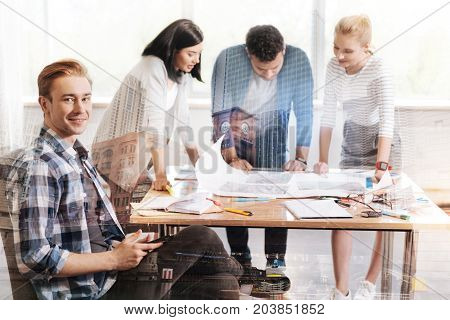 No free minute. Clever attentive team standing at the table and discussing work issues while their colleague smiling at you