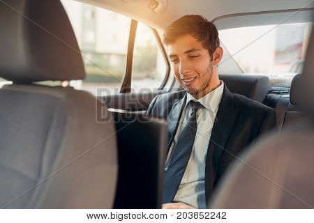 Businessman working while sitting in a car. Man beeing driven to work in his limo. Suit and tie businessman in the back seat using laptop while the driver is driving.
