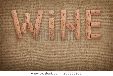 Word WINE shaped by natural wooden wine bottle corks of different vintage years over background of jute canvas