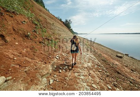 Girl Explores Steep Rocky Banks of the Northern Dvina River Situated in Taiga Forest. Back view.