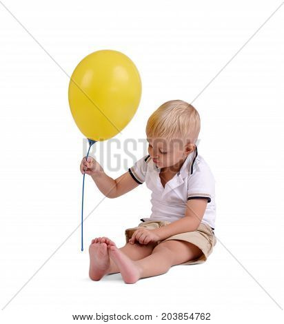First birthday - happy baby boy with balloons on white background. A boy in a white T-shirt is playing with a yellow balloon, isolated in a white background. Good day, perfect time. Birthday boy.