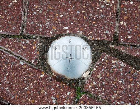 An Metal Circle Sign On The Ground Reading N R A