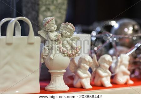 figurines of angels and a bag on a shelf in a store