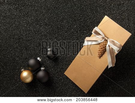 gift booklet with Christmas tree decorations on a black grainy background. flyer with ribbon on black grainy background