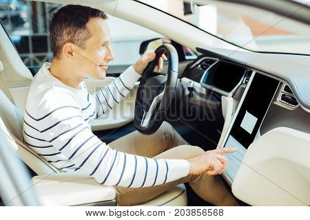 Male driver. Nice pleasant good looking man sitting in the car sear and pressing the button on the sensory panel while starting his car