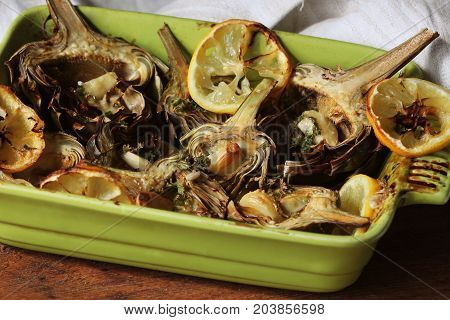 fried artichokes with garlic and lemon on pan .