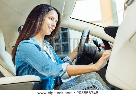 I like driving. Delighted nice beautiful woman sitting behind the wheel and starting her car while being ready to go