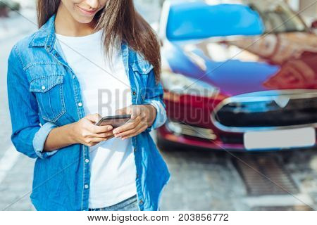 Modern igen. Attractive pleasant young woman standing on the street and holding her smartphone while using it
