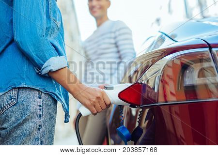 Gas station. Nice pleasant young woman holding a fuel nozzle and refilling her car while being at the gas station