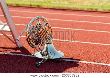 a french horn wired for sound waiting to perform
