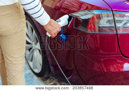 Auto refueling. Nice handsome adult man standing near his car and refueling it with a fuel nozzle while being at the gas station