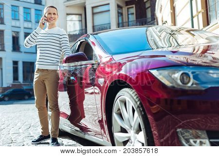 Distance communication. Delighted nice adult man holding his cell phone and listening to his interlocutor while opening the door of his car