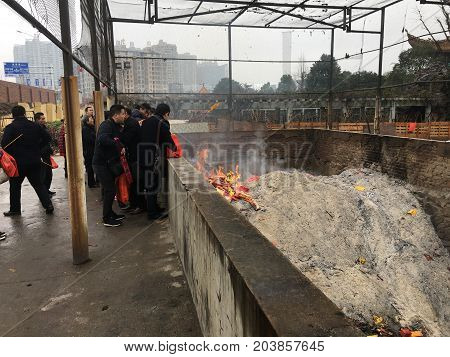 Wuhan China, 2 February 2017: Chinese people burning papers and incense at Guiyuan buddhist temple during chinese new year and huge ashes pile