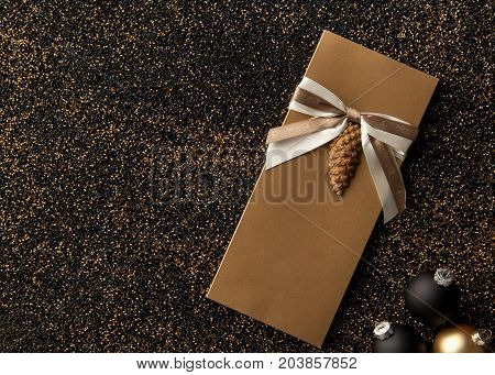 gift booklet with Christmas tree decorations on a golden grainy background. flyer with ribbon on a black golden grainy background