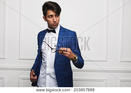 Handsome young brunette man wearing blue check jacket white shirt holding glasses looking away.