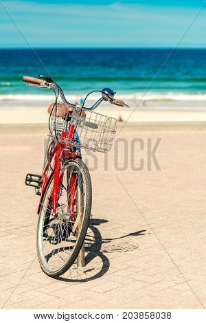 Red vintage retro styled bicycle with basket parked at Manly Beach Sydney Australia