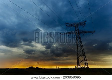 High Voltage Power Lines And Transmission Towers At Sunset. Poles And Overhead Power Lines Silhouett