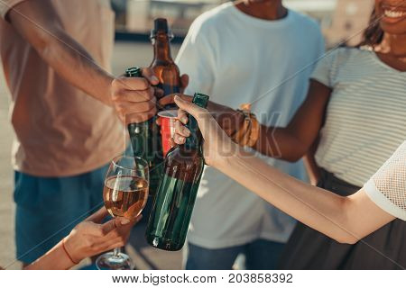cropped shot of people clinking with alcohol bottles and glasses