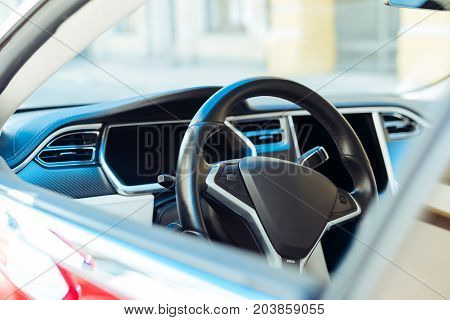 Modern automobile. Close up of a steering wheel of a modern expensive automobile being parked on the street