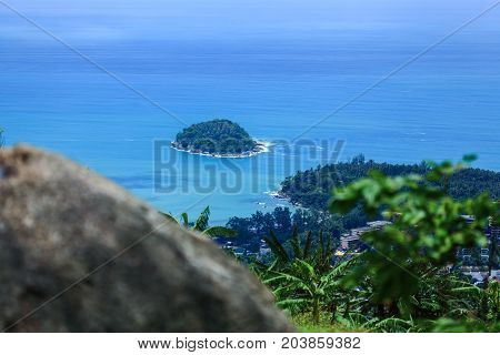 The distant island. A small tropical island. View of the island from the high mountains. The shore is covered with dense vegetation. Tall palm trees by the ocean. A wide blue sea.