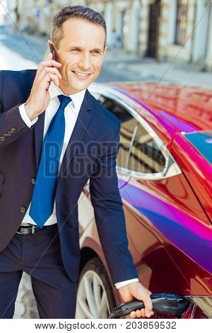 Good news. Happy delighted successful businessman smiling and talking on the phone while being at the gas station