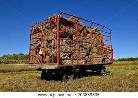 A load of baled straw in a hay wagon is parked in a field of wheat stubble