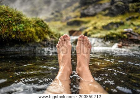 Woman's legs bathing in a hot spring in the Landmannalaugar mountains in Iceland.