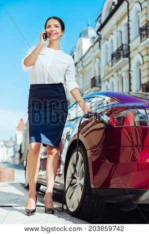 Always busy. Confident intelligent good looking businesswoman having a phone conversation and discussing work while refilling her car
