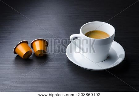Modern Shot Of Espresso Cup And Capsules