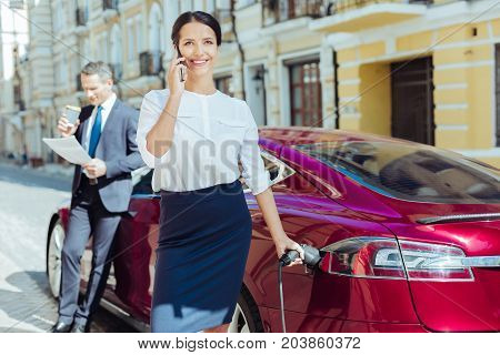Ability to multitask. Attractive smart positive businesswoman smiling and having a phone conversation while refueling her car