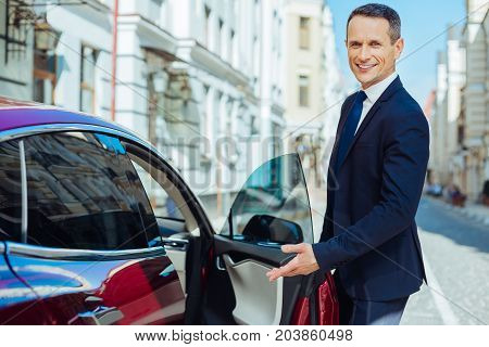 Invitation to sit. Joyful nice polite man smiling and pointing to the car sear while inviting you to get into the car