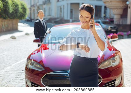 What time is it. Cheerful positive nice businesswoman smiling and checking the time while talking on the phone