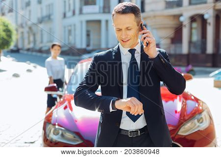 Time is money. Serious smart busy businessman talking on the phone and looking at his watch while checking the time