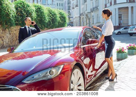 Business meeting. Delighted nice business partners talking to each other and getting into the car while going on the business meeting