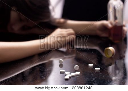 a drug addict not conscious on the table with several pill spilled on table near bottle of alcohol.