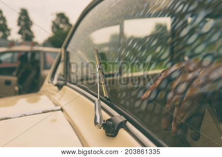 Reflection of the sky in the windshield of a vintage car against the backdrop of a salon with leather gloves on the steering wheel