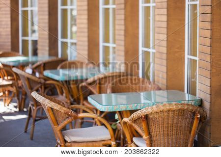 Beautiful and cosy summer terrace with light brown wicker chairs and blue tables stand opposite the windows of cafe. Shallow dof. Focus on foreground.