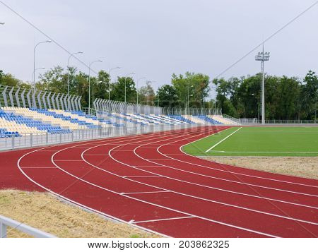 Sport and fitness concept. Equipment for sports stadium: colorful treadmills, blue and yellow stands, bright field, grey lights in the stadium. Green trees and blue sky on the background.