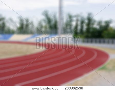Blur picture of sport and fitness concept. Equipment for sports stadium: colorful treadmills, blue and yellow stands, bright field, grey lights in the stadium. Place without people.