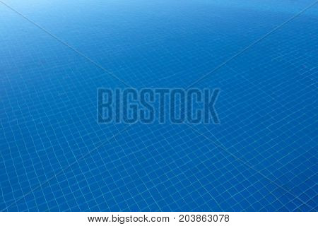 Clear blue water in the pool, through the sunlight. Water background.